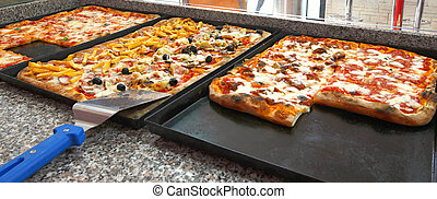 Square pieces of pizza. - Counter of the pizzeria with trays...