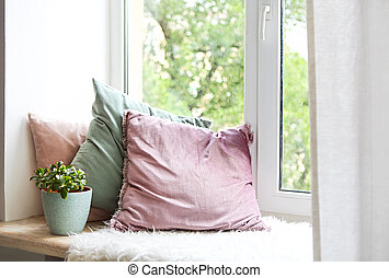 Square pillows, plaid and plant at the window