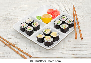 Square plate with a set of rolls on a wooden table. Chopsticks, ginger, lemon. Side view