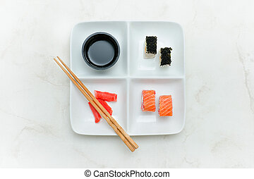 Square plate with rolls and sushi on a white table. Soy sauce and ginger. Top view