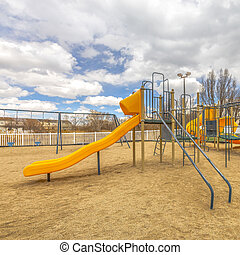 Square Playground with slides and swings under the blue sky filled with puffy clouds
