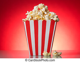 Square red and white striped popcorn box on a bright background