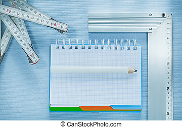Square ruler checked notepad pencil tape measure.