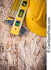 Square ruler construction level building helmet wooden meter on chipboard.