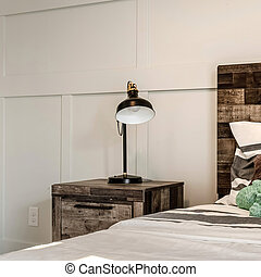 Square Single bed with brown wooden headboard and side table with modern lamp