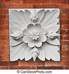 Square stone decoration on the wall of the temple on Bali island - lotus flower