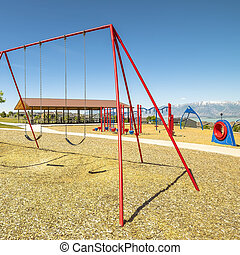 Square Swings on a park with playground pavilion lake and mountain in the background