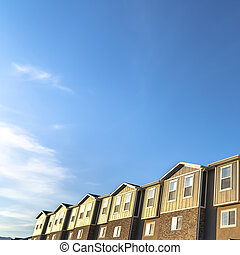 Square Townhouses with brick wood and concrete wall against blue sky on a sunny day