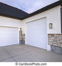Square Two garage doors positioned at right angles sharing a paved forecourt in close up