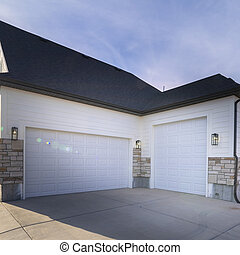 Square Two garages with paved forecourt and closed white doors on a housing estate