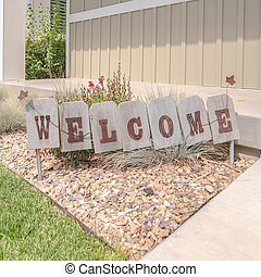 Square Welcome sign in front garden of traditional home