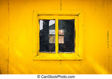 Square window on a yellow wall