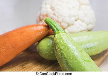 Squash cauliflower and carrots on a cutting board