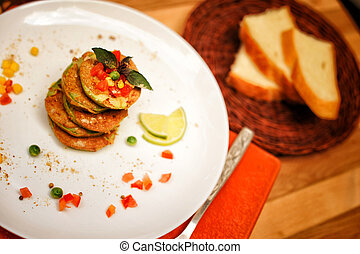 Squash fritters served on a plate and whole grain bread