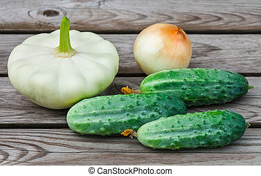 Squash, onions and cucumbers on table