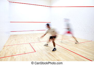 Squash players in action on a squash court (motion blurred ...