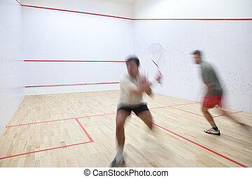 Squash players in action on a squash court (motion blurred...