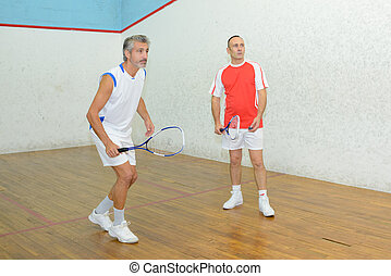 squash players in action on a squash court