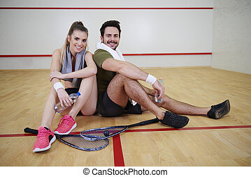 Squash players taking a break on floor