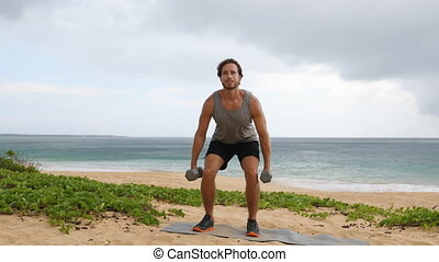Squats fitness exercise - man doing Dumbbell Squats workout exercising legs outdoor on beach. Fit male athlete showing exercises. SLOW MOTION.