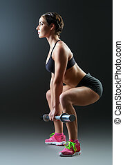 squatting - Strong young woman with beautiful athletic body...
