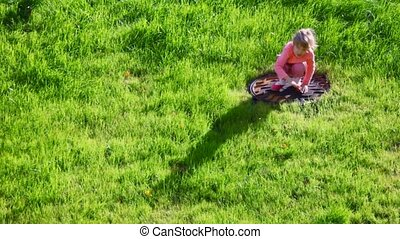 squatty little girl on green grass background