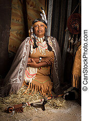 Squaw with peace pipe - Weathered mature tribal female...