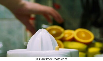 Squeezing fresh juice out of ripe tasty oranges and grapefruits