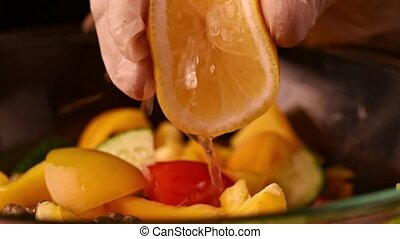 Squeezing lemon on salad in slow motion