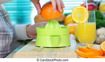 Squeezing orange - female hand squeezes orange juice on a...