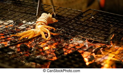 Squid Cooked on the Grill Grate in Night Food Market, Thailand Street Food. Thailand