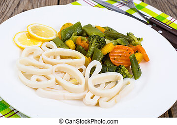 Squid rings with vegetable garnish. Studio Photo