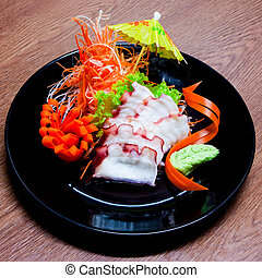 Squid Sashimi in black plate on wood table