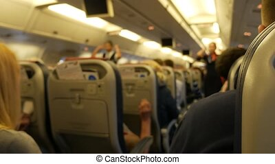 Srewards standing between seats ia airplane and pointing at...