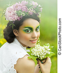 Portrait of a young girl with tulips, lily of the valley and pink peony in her hair