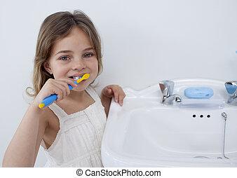 stående, av, a, liten flicka, rensning, henne, tänder