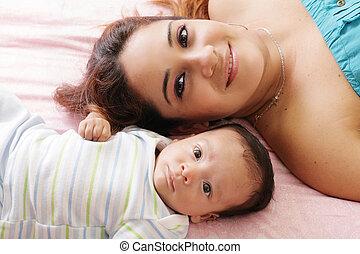 stående, av, lycklig, ung, attraktiv, hispanic, mor, lögnaktig, med, henne, baby, blomsterbädd