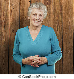 stående, av, senior woman, stående, mot, a, trä vägg