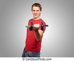 stående, av, ung man, med, vikter, över, grå, bakgrund