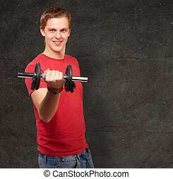stående, av, ung man, med, vikter, mot, a, grunge, vägg