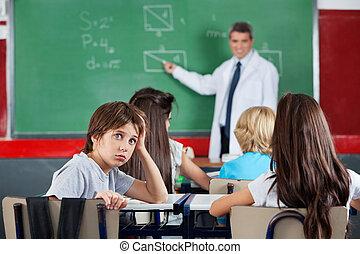 stående, av, ung, skolpojke, böjelse, på skrivbordet