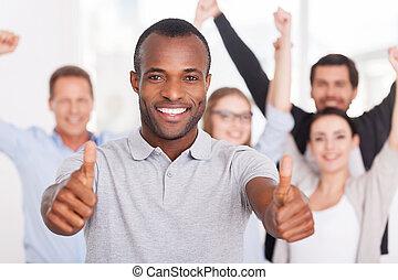stående, ha på sig, hans, grupp, affärsfolk, uppe, visande, ung, dig, team., medan, tummar, bakgrund, afrikansk, leende herre, tillfällig, lycklig