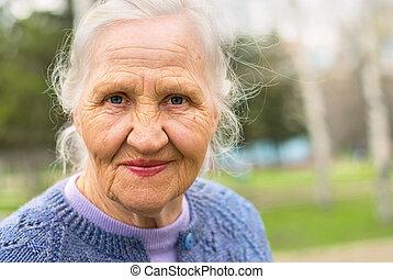 stående, le, äldre kvinna