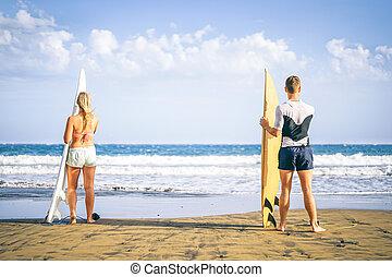 stående, livsstil, begrepp, bränning, prålig, hälsosam, strand, par, ha, -, ung, dag, hög, folk, förberedande, vågor, nöje, sport, vänner, surfbräda, surfarear