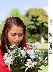 stående, parkera, blomningen, medan, nedåt, se, kvinna, ung