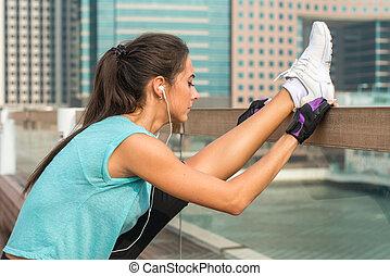 stående, stad, kvinna, skott, henne, headphones., vertikal, splittring, sträckande, ung, uppe, arbete, gata, musik, träningen, lyssnande, fitness, ben, nära, ute