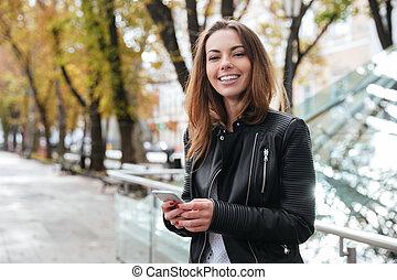 stående, stad, smartphone, glad, kvinna, användande