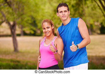 stående, ungt par, med, tumme uppe, gör, sportutbildning, fitness
