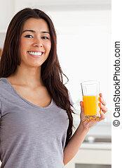stående, vacker, medan, holdingen, apelsinsaft, glas, kvinna