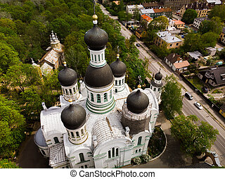 St. John the Forerunner orthodox church among cemetery with green trees with dome under reconstruction aerial view